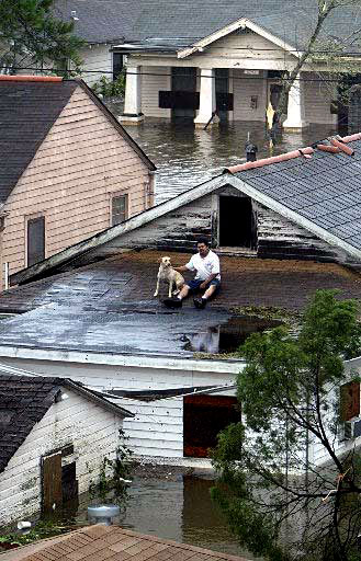 A Hurricane Katrina survivor rests with his dog as he awaits help