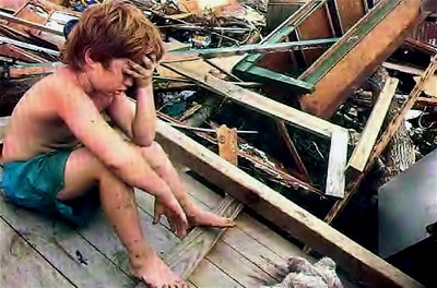 A distraught boy sits in disbelief amid the rubble